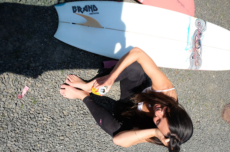 Photo from above of Jennifer Yih with a can of Blazing Bright sitting on the ground next to a surfboard