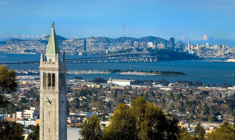 Sather Tower rises above UC Berkeley with San Francisco an the bay bridge in the background