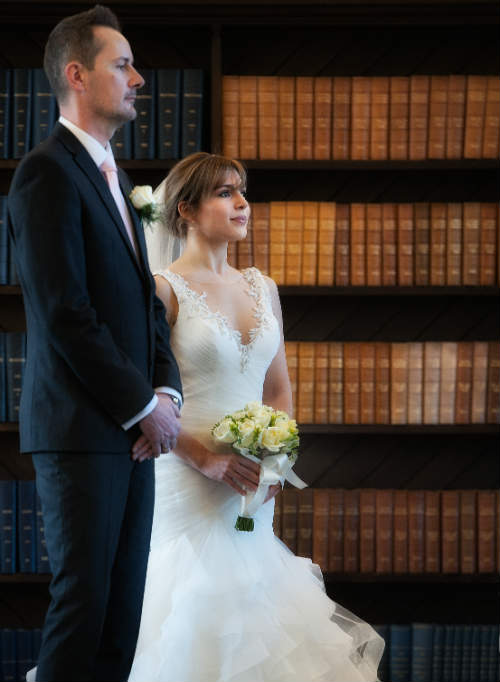 A wedding couple in front of a shelf of old, leather-bound books