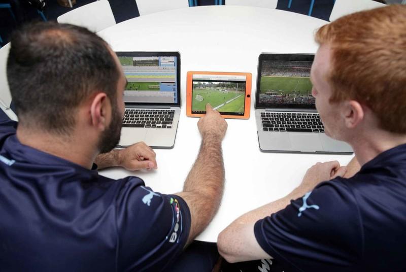 ノート PC とタブレットで試合の映像を見ている 2 人のサッカー選手