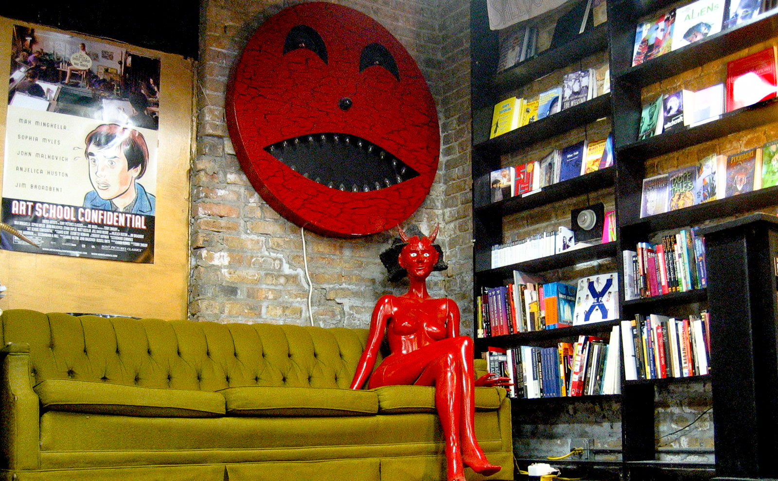 stage area in quimby's with green couch and red lady-devil mannequin