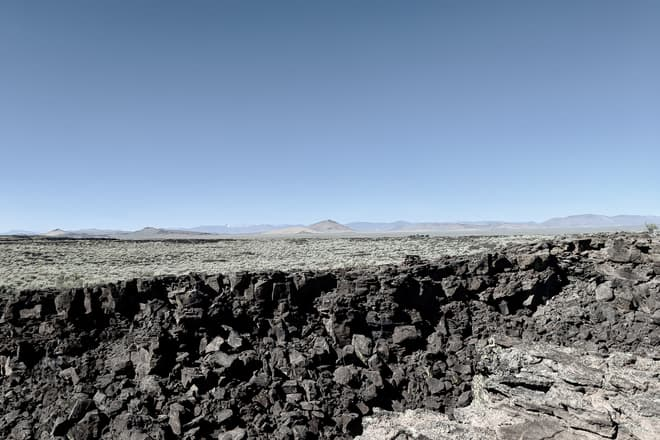 A U-shaped dark basalt boulder field, all that is left of a collapsed lava tube. Beyond it, desert scrubland, and finally distant mountain peaks.