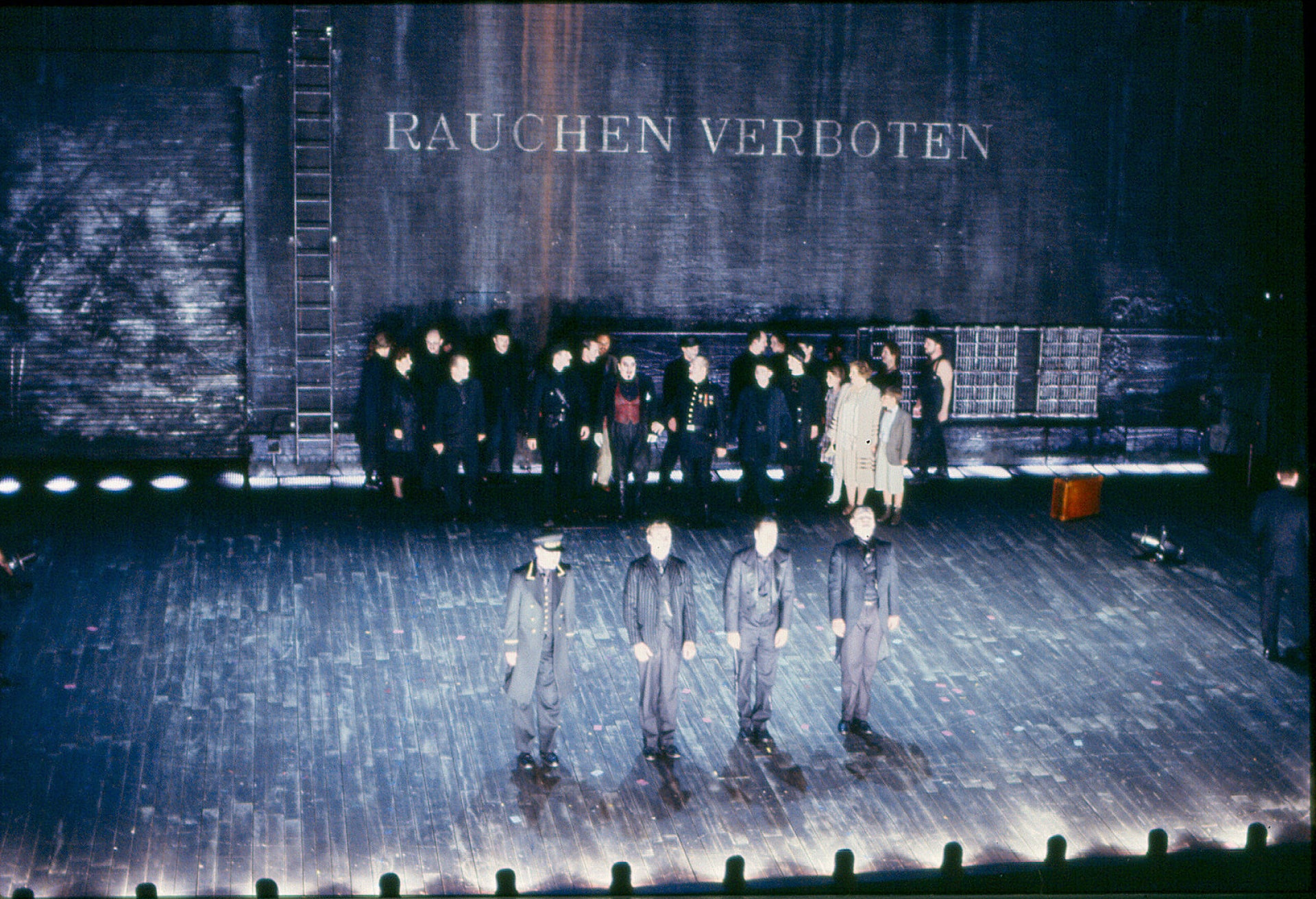 """Four men in grey stand in a row on stark foot lit stage, watched by small crowd against wall where """"Rauchen Verboten"""" is written."""
