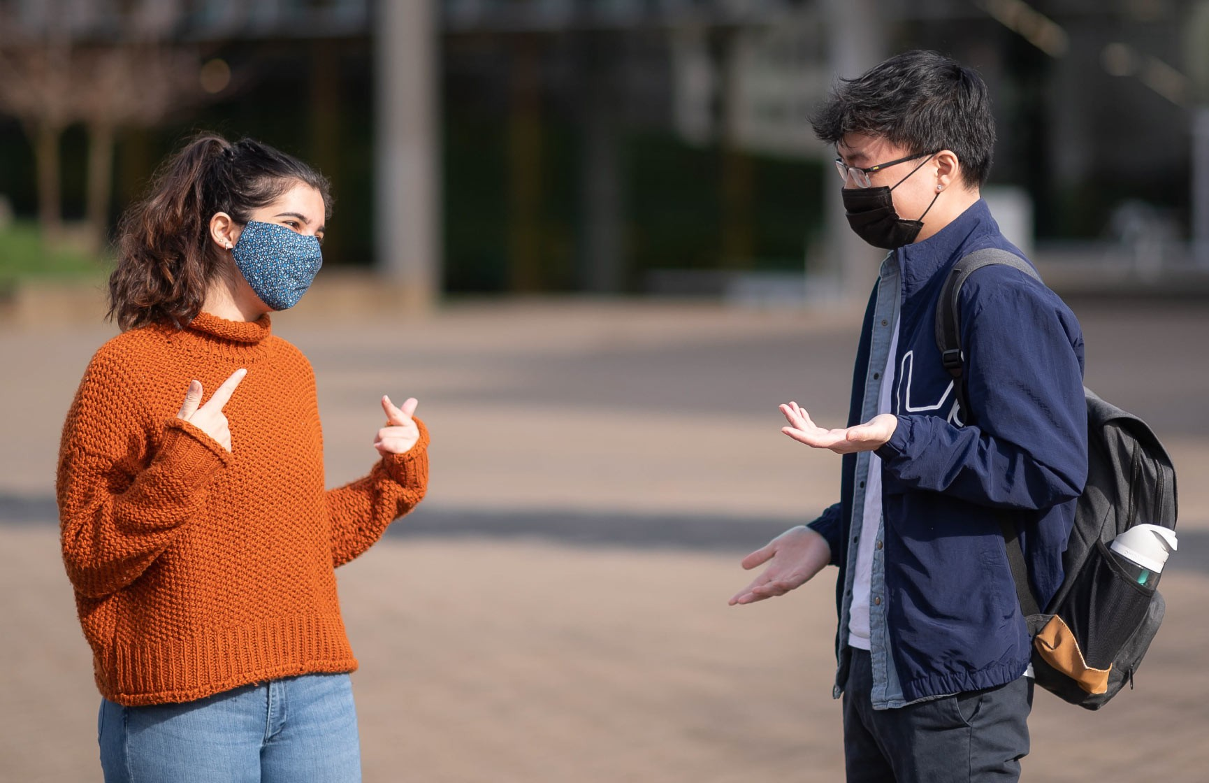 Two people wearing COVID-19 face masks use hand gestures to help communicate to each other