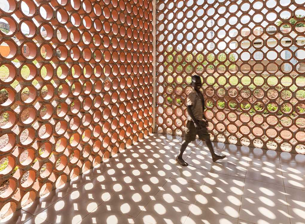 Young child standing inside courtyard with wall made up circular forms creating shadows