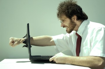 Homem com raiva quebrando um computador