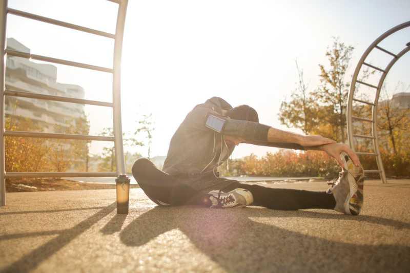 man stretching on pavement