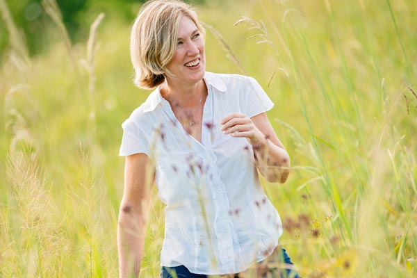 Sue Brighton smiling and standing in a field.