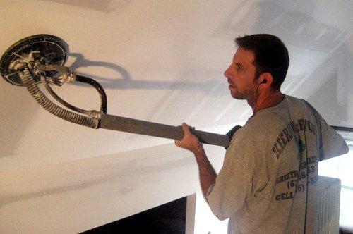 drywall contractor using vacuum sander