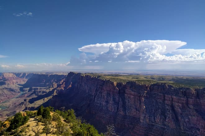 Looking across the South Rim of the Grand Canyon, and into the desert beyond. Rain clouds gather in the distance.