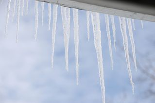 Icicles as a result of ice damming in clogged eaves - gutters checked - Eavestrough Inspection