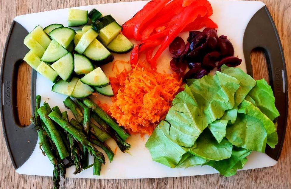 Cutting board with cucumber, lettuce, olives, carrot, asparagus, and red pepper.