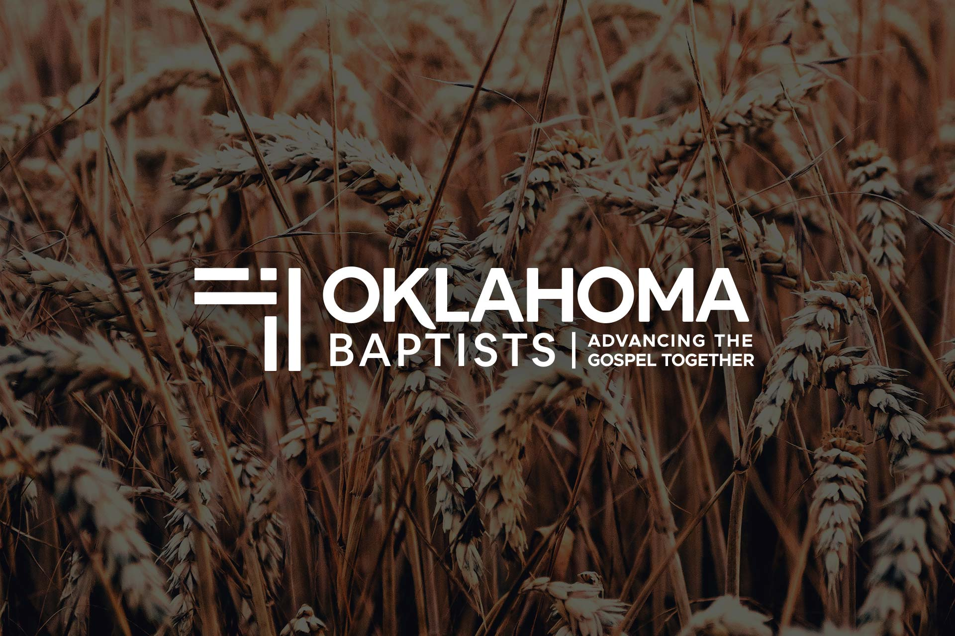 The Oklahoma Baptists logo over an image of wheat in an Oklahoma field.