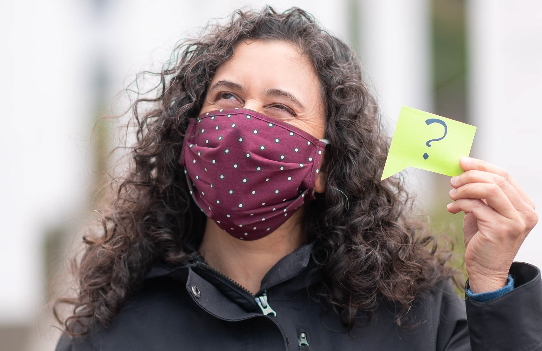 A person wearing a COVID-19 face mask holds up a sign with a question mark on it to indicate that they can't understand what people are saying