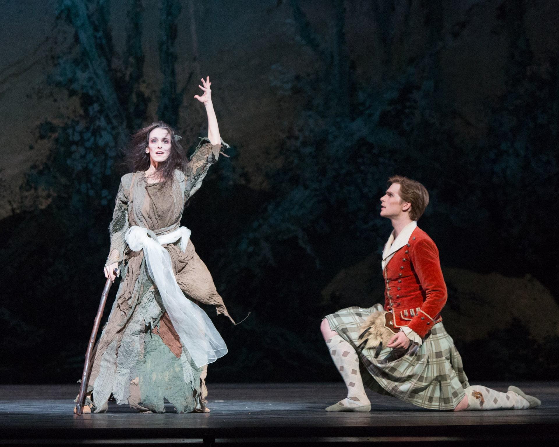 Ballerina in dress of rags gestures upward watched by kneeling dancers in kilt and red jacket.