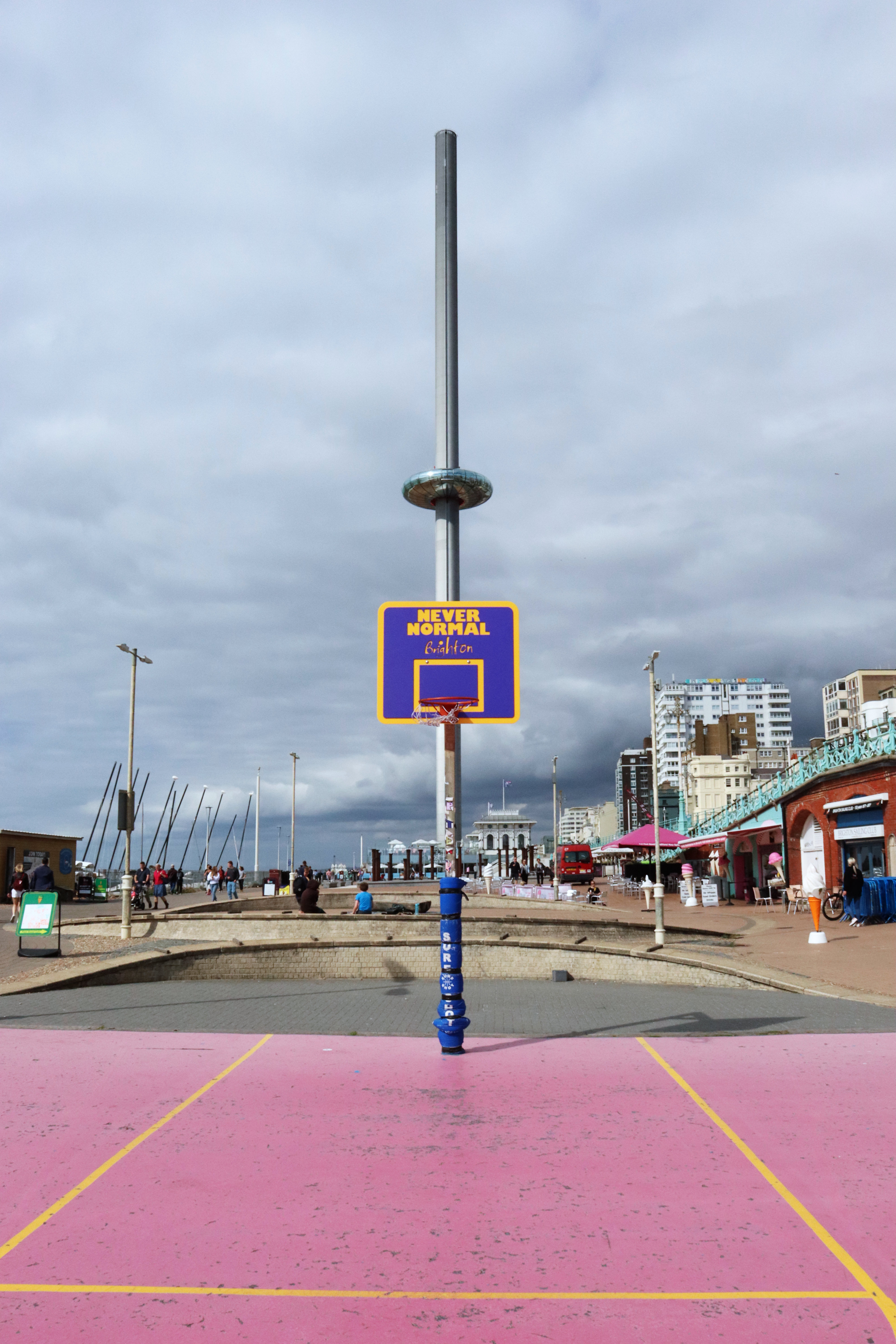 Basketball hoop on the western side of the basketball court on Brighton beach. Behind and aligned with the hoop, the I360 is ascending.
