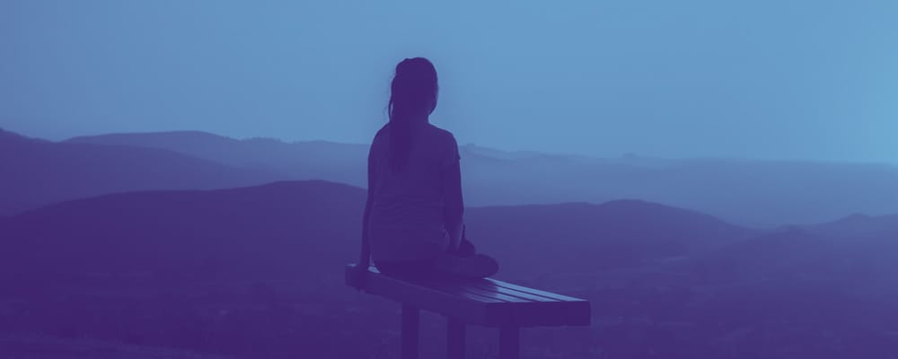 woman sitting on a bench overlooking mountains