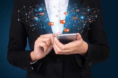 Photo of a woman in a business suit that is on a mobile phone with social network symbols floating off the screen.