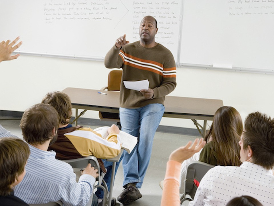 Postsecondary teacher asks classroom a question and picks on students to answer during his lecture.