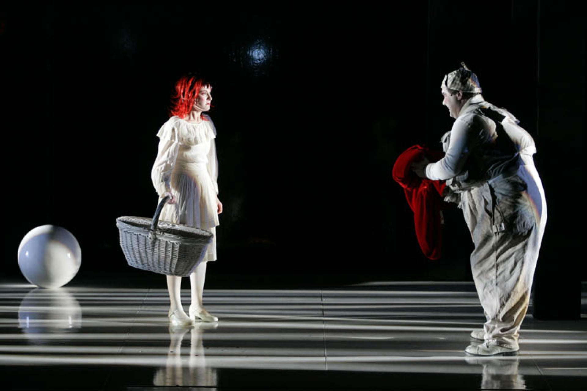 Red-headed girl in white dress carrying basket and man in checkered cap with red cape stand on white floor streaked with shadows near white ball.