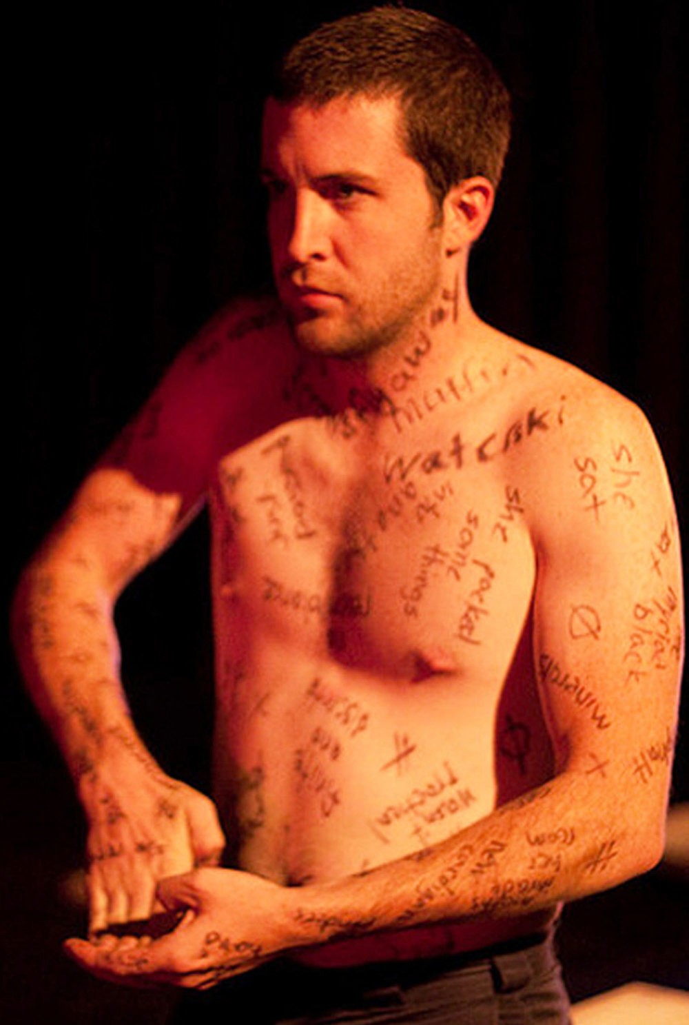 Shirtless man covered in writing, bends his fingers bakc