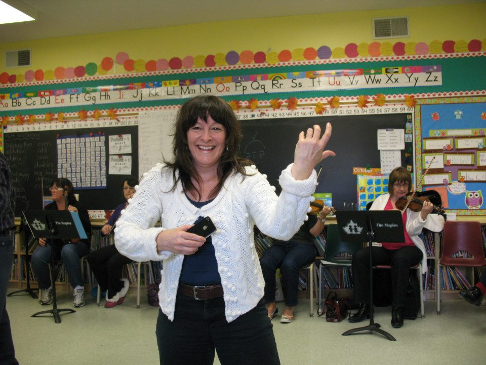 Cindy holding an imaginary fiddle, and smiling, standing in the middle of a classroom.