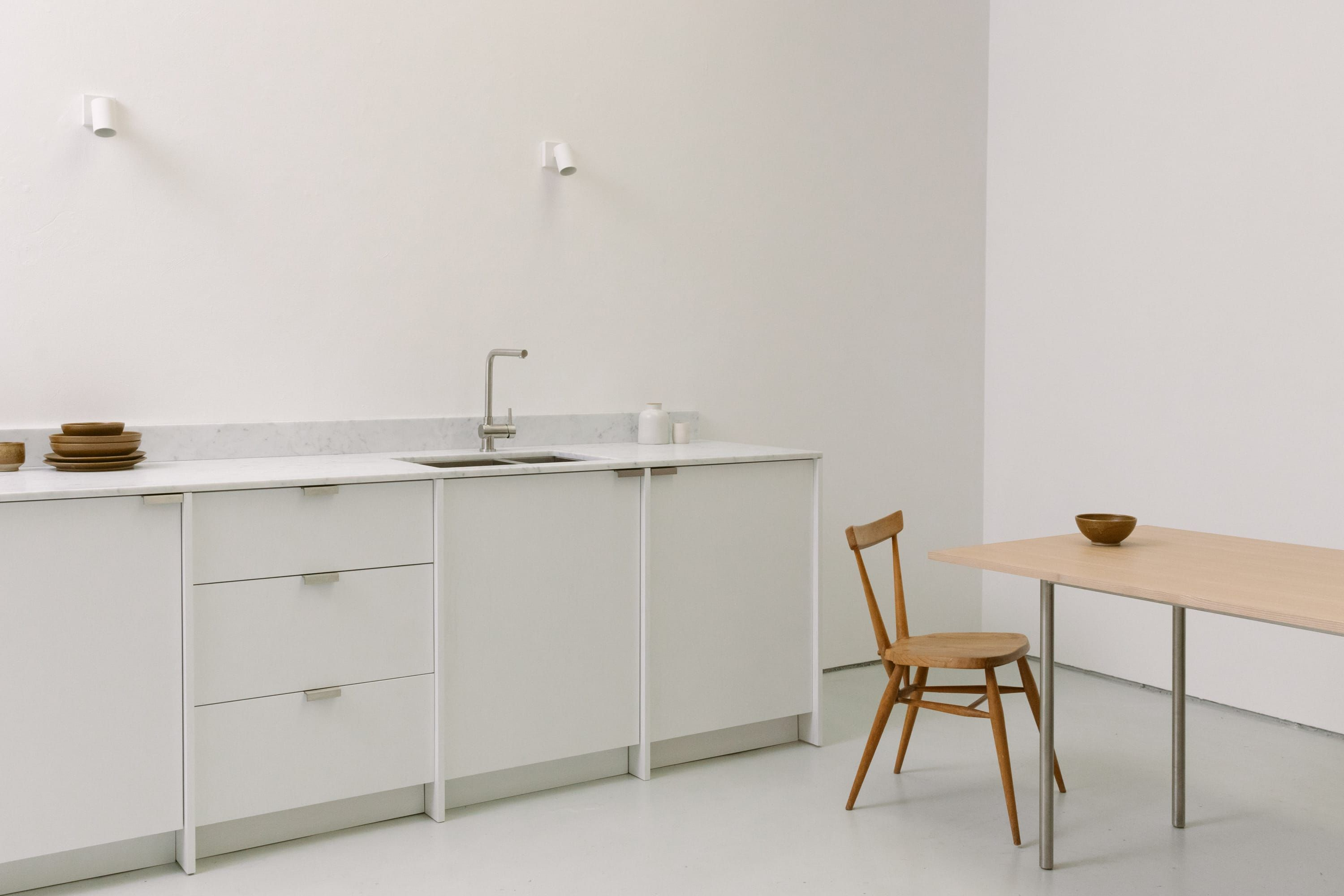 White painted From Kitchen with Carrara marble worktop, dining table and chair.