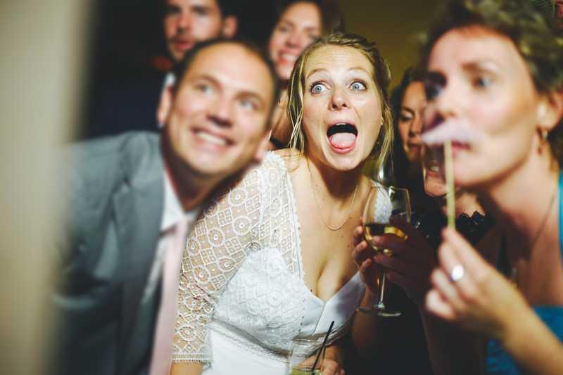 Gasten van een bruiloft poseren voor een photobooth met attributen