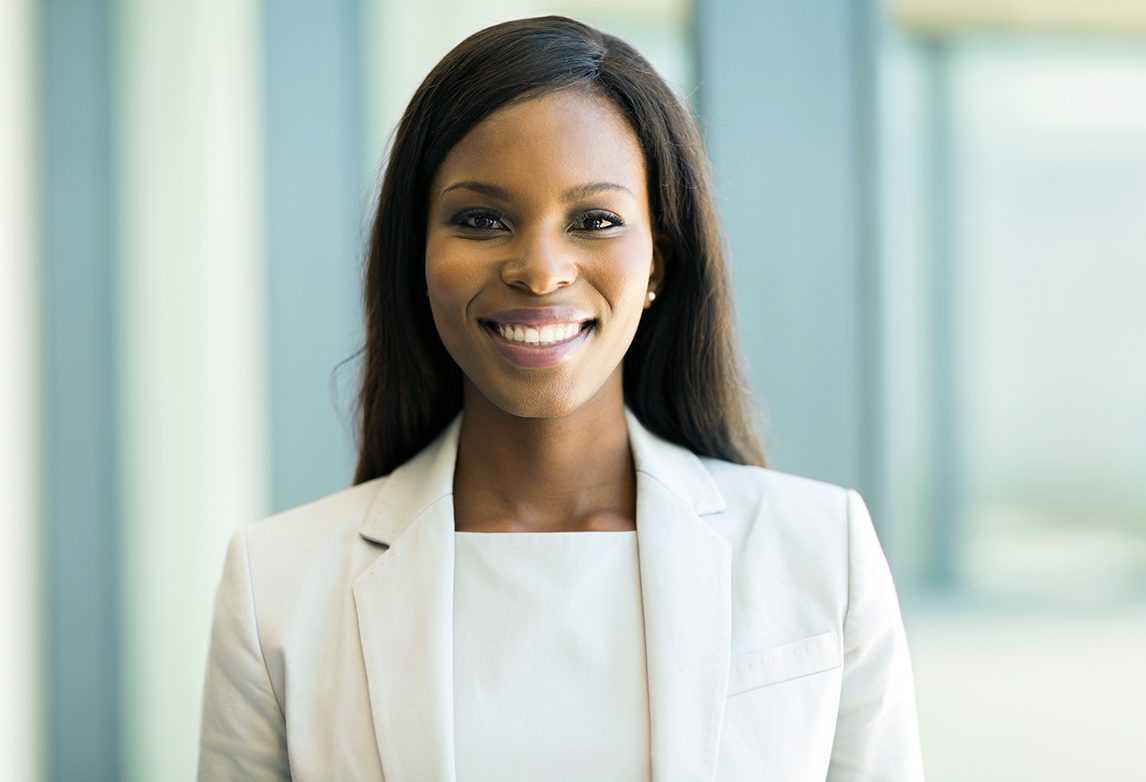 A young woman in professional attire flashes a big smile.