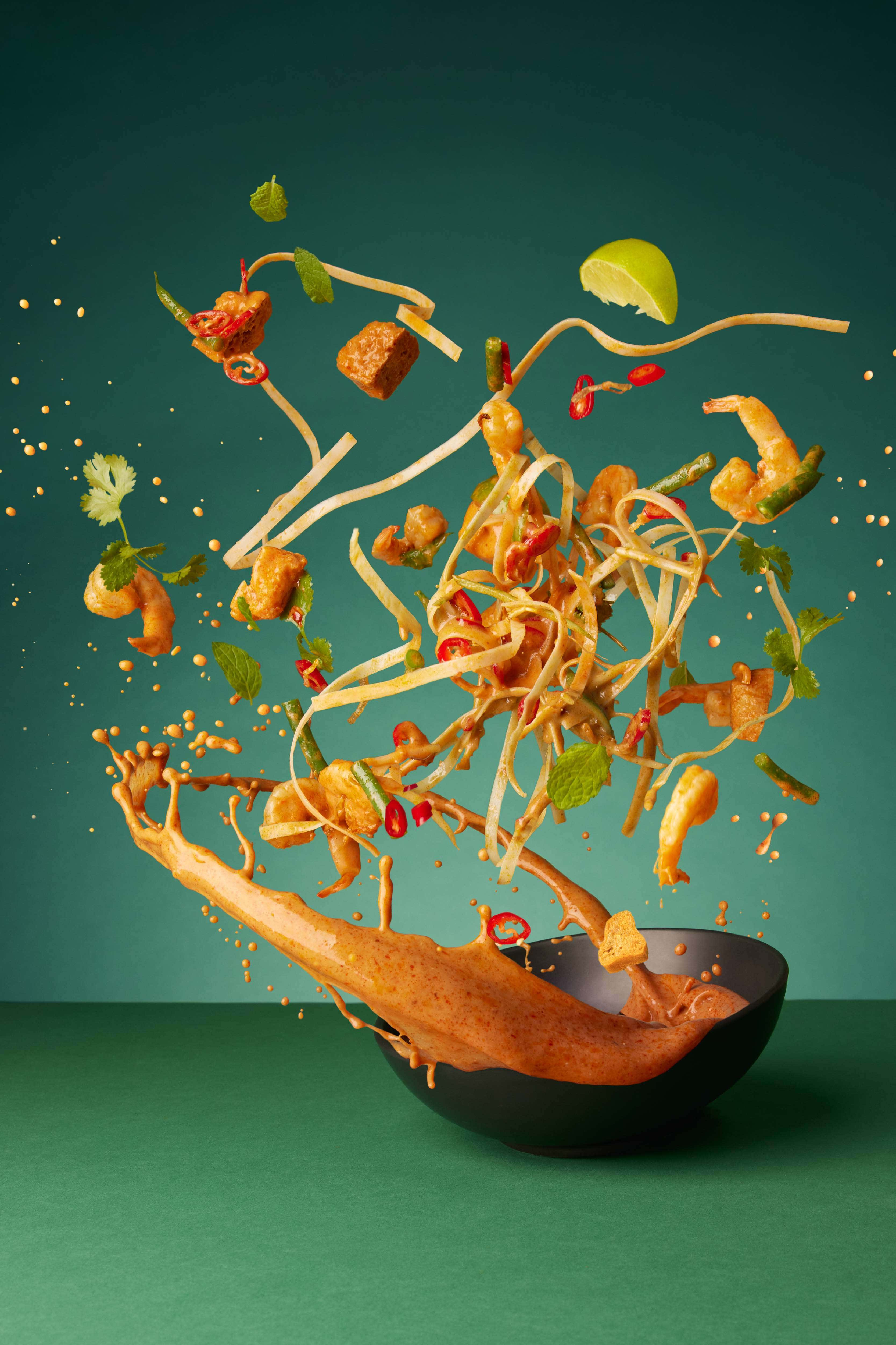 noodles flying through the air with prawns, chillis and tofu and other ingredients