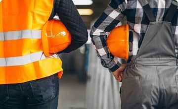 Sécurité du travail - 2 employés de dos côte à côte,  avec leurs casques orange sous le bras. L'un porte un gilet de sécurité orange, l'autre est en salopette grise.