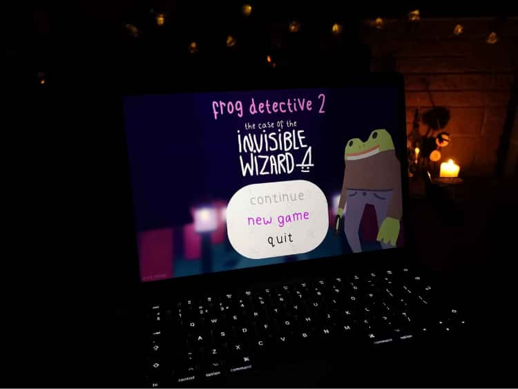 A picture of my laptop with the menu of Frog Detective 2 on the screen. The menu displays the frog detective, the title of the game, Frog Detective 2: The Case of the Invisible Wizard and the option to start a new game highlighted.