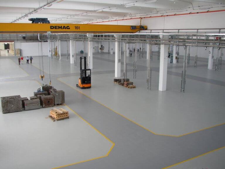 Pavimento industriale in resina antiscivolo con segnaletica orizzontale e corsie su resina.