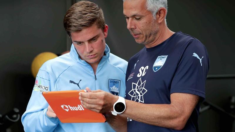 Hudl タブレットでシドニー FC 選手に分析を見せるコーチ