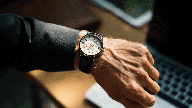 Accountant, business person, staff member, business owner looks at watch to see time and increase efficiency above wooden desk with laptop, tablet, notepad #business