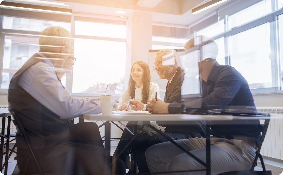 Excellence opérationnelle - Réunion 5 personnes (hommes et femmes) assises autour d'une table