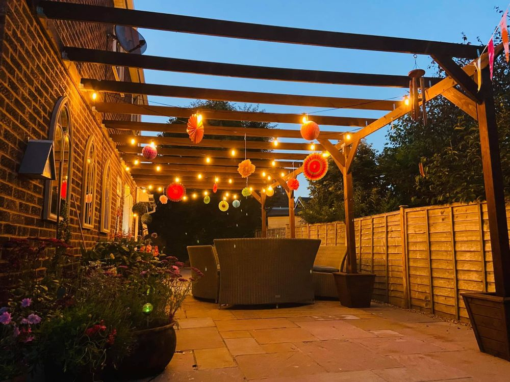 An example of a pergola, in the evening with lanterns and lights with a dining table underneath it.