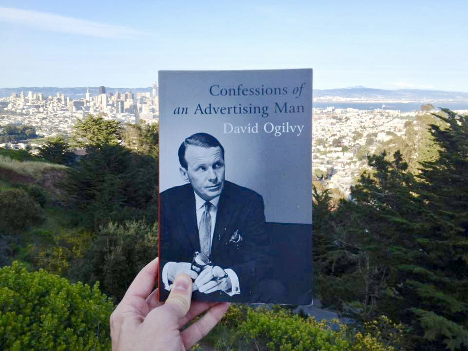 The book held up against a backdrop of nature and an urban skyline