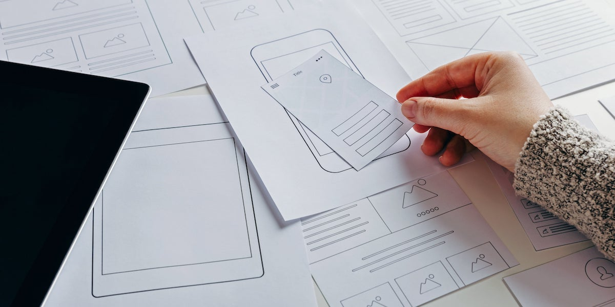 A UI designer works on a wireframe of a mobile app interface