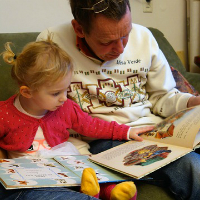 A man reading with a child