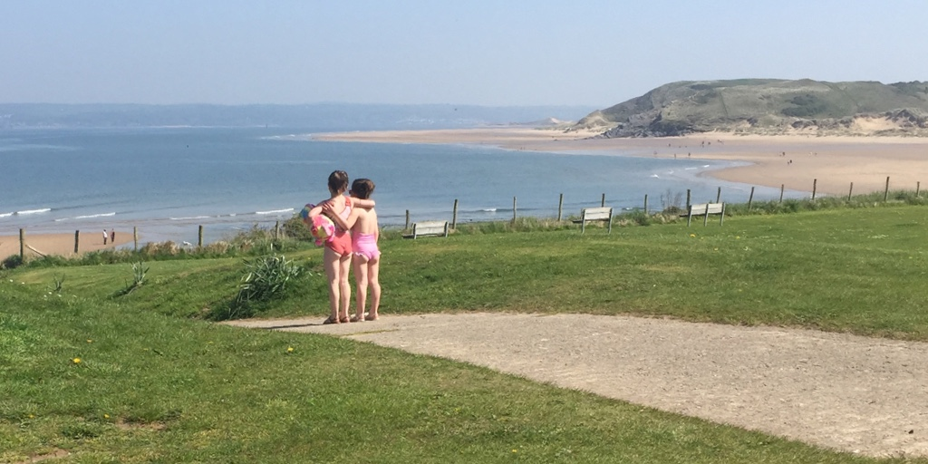 2 girls standing together, looking down at the beach on a sunny day