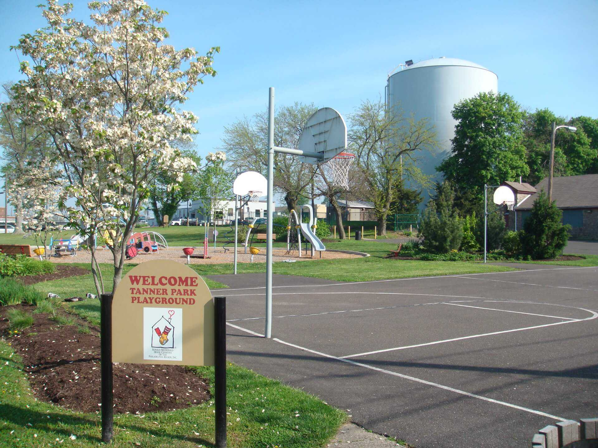 welcome tanner park sign with basketball court and playground