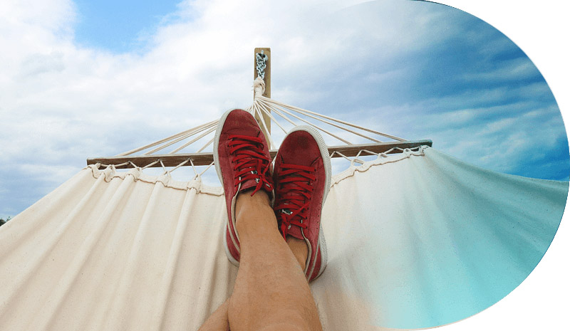 Legs on a hammock in front of blue sky