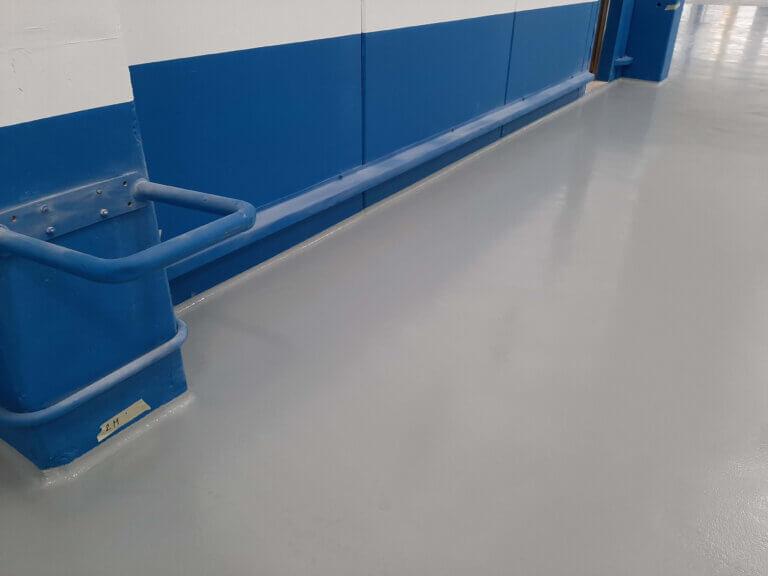 Dettaglio del battiscopa integrato con la pavimentazione in resina.
