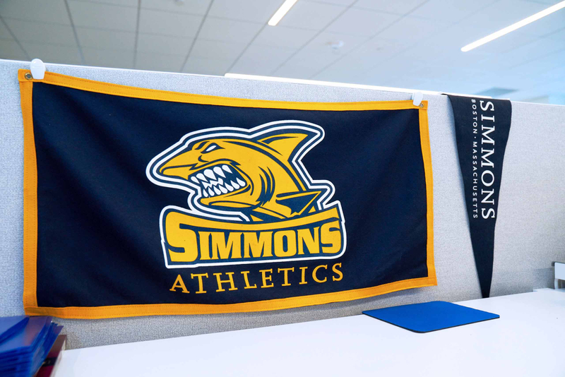 A Simmons University Athletics banner and pennant hanging in a cubicle