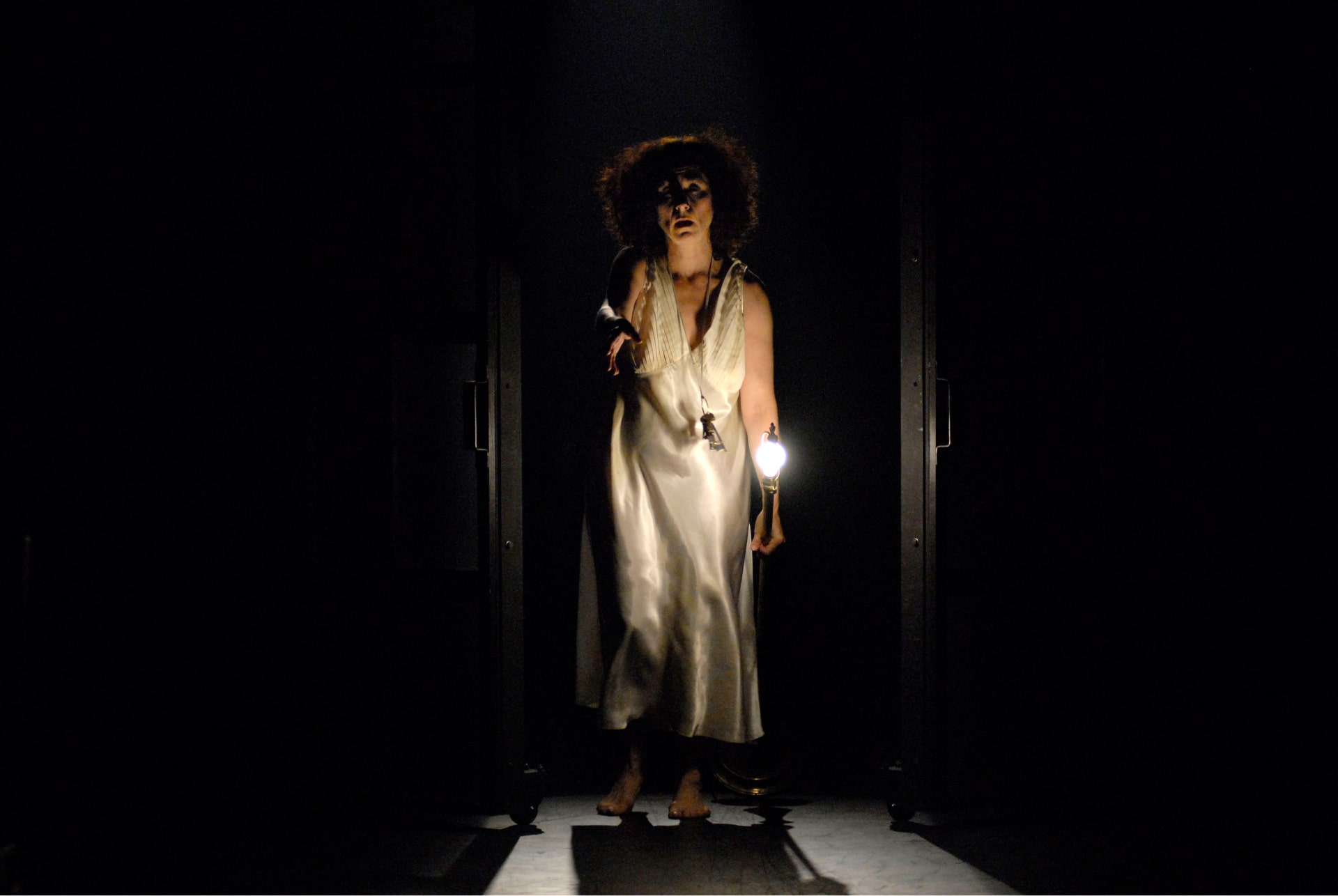 Woman in white silk slip stands backlit in doorway carrying lit unshaded floor lamp, arm outstretched.