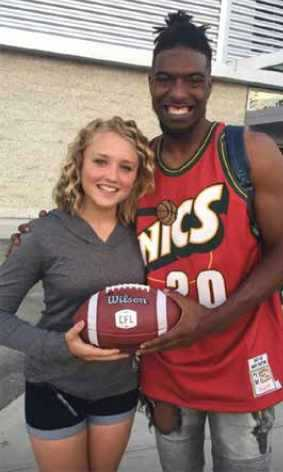 Duran Carter and Paige Hansen holding a football