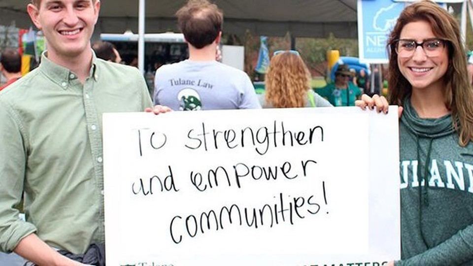 A man and a woman holding a sign written To Strengthen and empower communities
