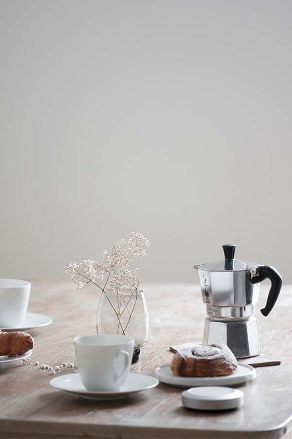 Nuimo Control white on a wooden kitchen table surrounded by coffee pot, white plates with food and coffee cups