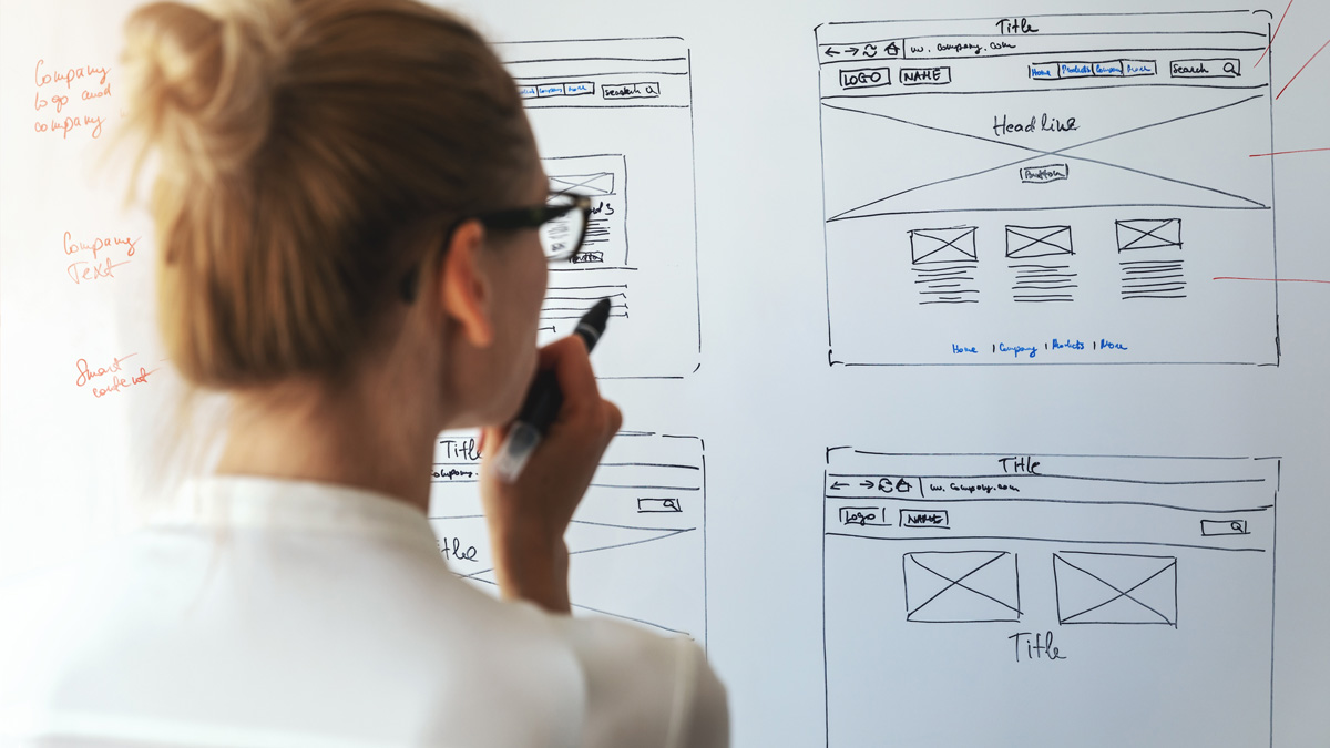 UX designer looking at a whiteboard with rough prototypes